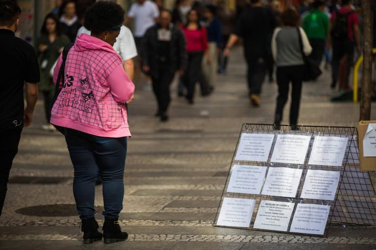 Mulher negra observa placas com ofertas de emprego no centro de São Paulo