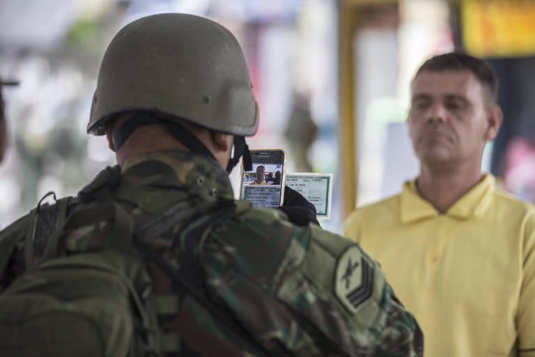 Homem das Forças Armadas fotografa morador durante operação na Vila Kennedy, na zona oeste do Rio