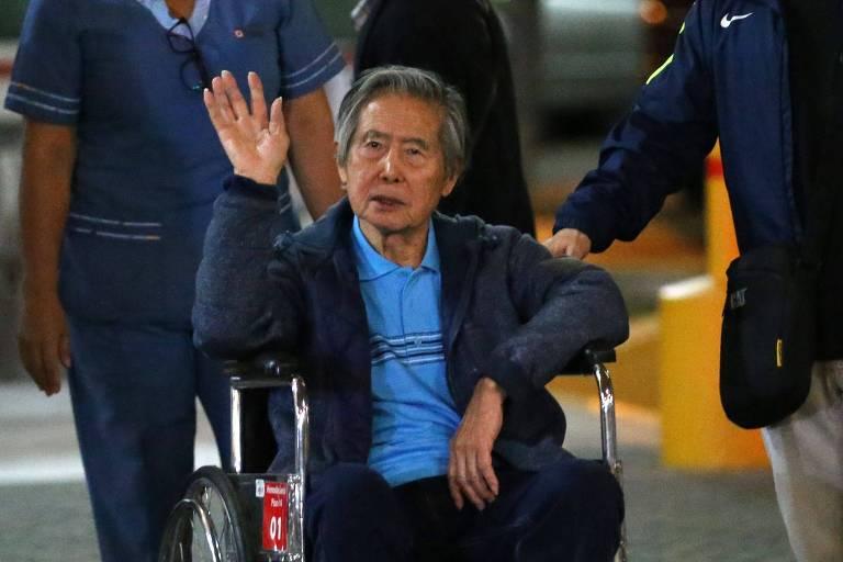 Em uma cadeira de rodas, o ex-presidente do Peru Alberto Fujimori acena ao deixar o hospital onde estava internado em Lima