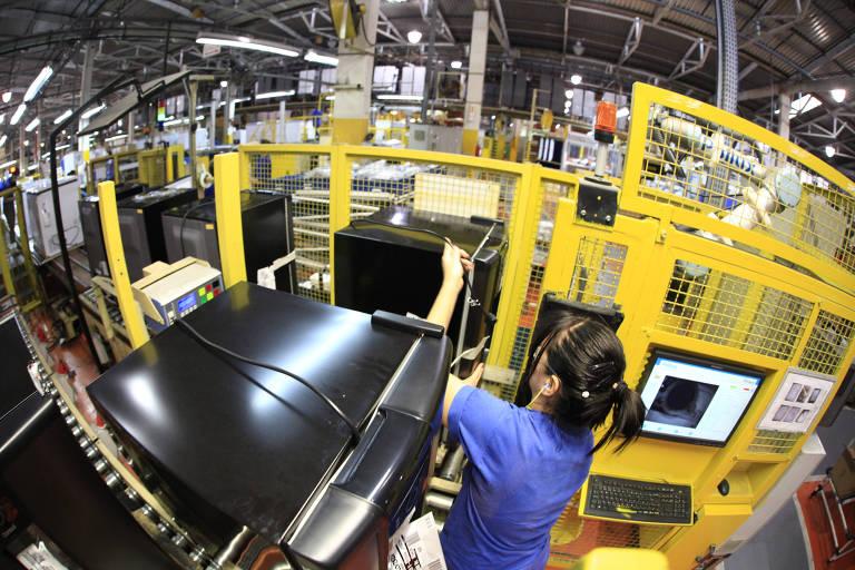 Uma funcionária vestida de azul manuseia uma máquina em uma fábrica
