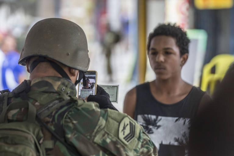 Militar fotografa documento de morador do Rio durante operação na Vila Kennedy, na zona oeste da cidade