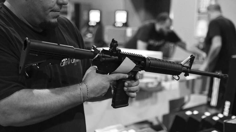 Homem analisa fuzil em feira de armas na Flórida