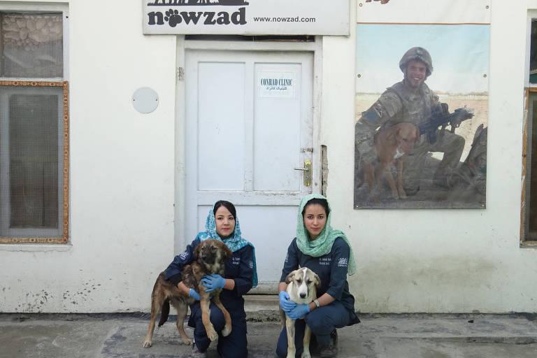 As veterinárias Tahera Rezaei (dir), 26, e Malalai Haikal, 24, diante da clínica da ONG de resgate de animais Nowzad, em Cabul, no Afeganistão