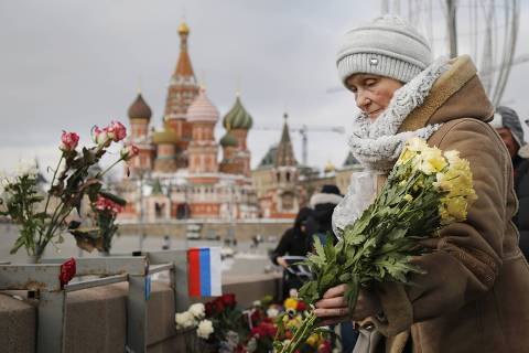 A woman lays flowers at the place where Russian opposition leader Boris Nemtsov was gunned down, next to the Kremlin Wall, in Moscow, Russia, Sunday, Feb. 25, 2018. Thousands of Russians took to the streets of downtown Moscow to mark three years since Nemtsov was gunned down outside the Kremlin. (AP Photo/Alexander Zemlianichenko) ORG XMIT: XSG106