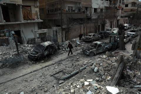 TOPSHOT - A picture taken on February 25, 2018, shows a Syrian man walking next to damaged buildings following regime air strikes in the Syrian rebel-held town of Douma, in the besieged Eastern Ghouta region on the outskirts of the capital Damascus. New regime air strikes and heavy clashes shook Syria's rebel enclave of Eastern Ghouta on Sunday despite a UN demand for a ceasefire to end one of the most ferocious assaults of Syria's civil war. / AFP PHOTO / HAMZA AL-AJWEH