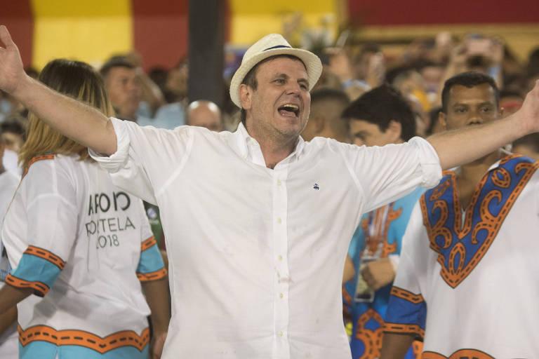 O ex-prefeito do Rio de Janeiro, Eduardo Paes, no desfile da Portela, na Marquês de Sapucaí. Paes está de braços abertos cantando com a escola de samba. Veste camisa branca e chapéu panamá