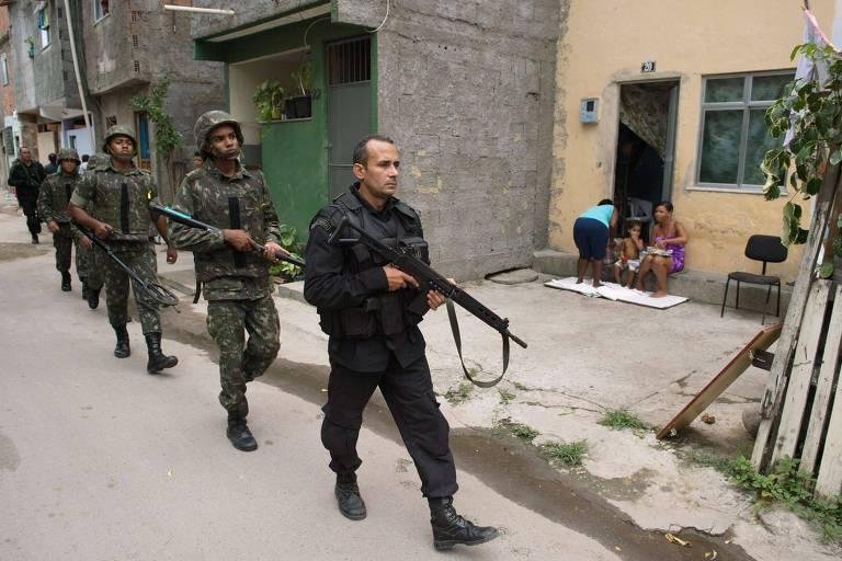 Policial do Bope (Batalhão de Operações Especiais) a frente de militares do exército, patrulham favela no Complexo da Maré (RJ)