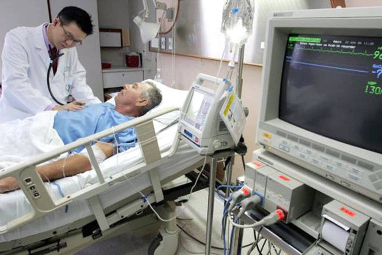Médico examina paciente em cama de hospital, ao lado de monitor com batimentos cardíacos