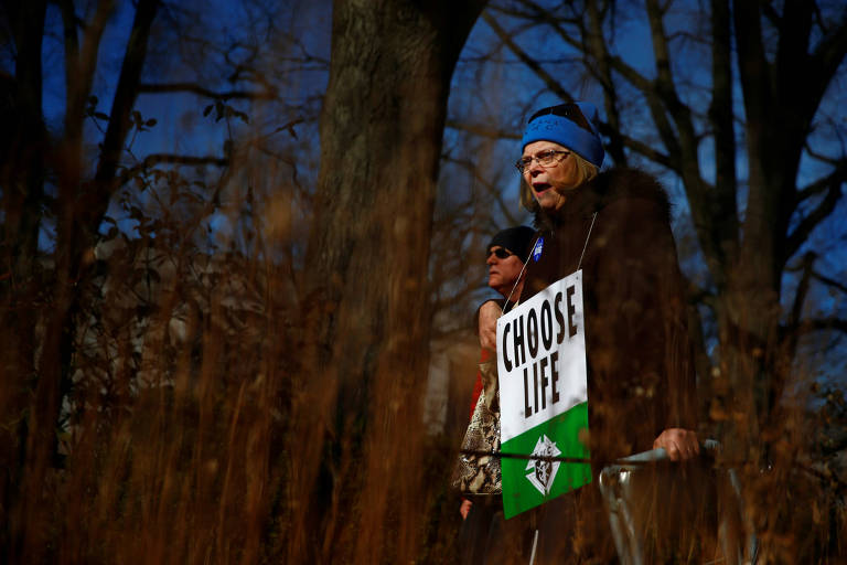 Manifestante com cartaz pendurado no pescoço com a frase 'Escolha a Vida' chega a ato contra o aborto em Washington