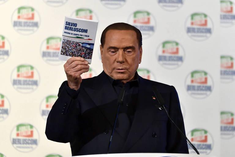 O ex-primeiro-ministro Silvio Berlusconi mostra livro de sua autoria durante evento de campanha para a eleição na Itália