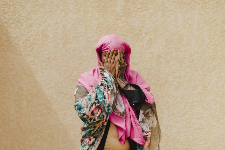Vestida com lenços e o véu islâmico uma das candidatas a asilo na França esconde o rosto após ser entrevistada em Niamey