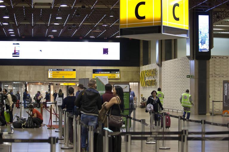 Pessoas esperando em fila, em terminal de aeroporto