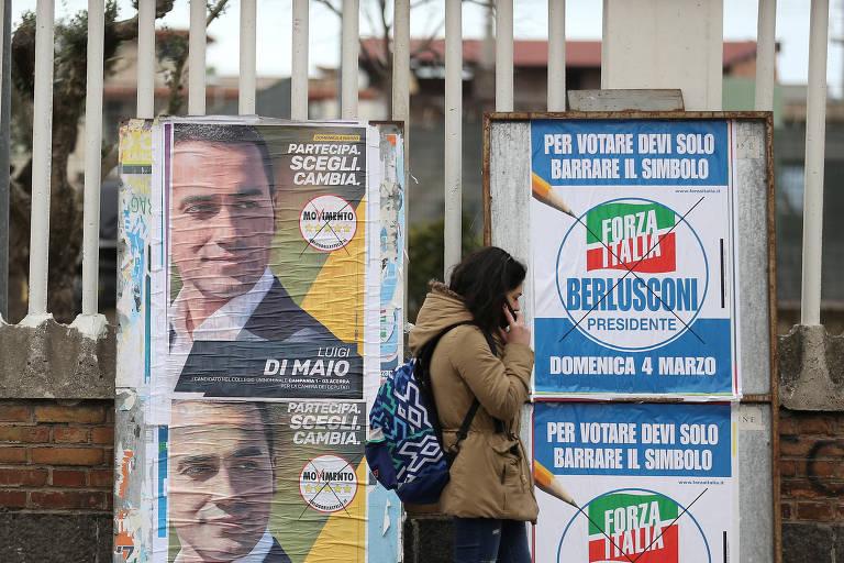 Mulher passa por pôsteres de candidatos em Pomigliano D'Arco, perto de Nápoles