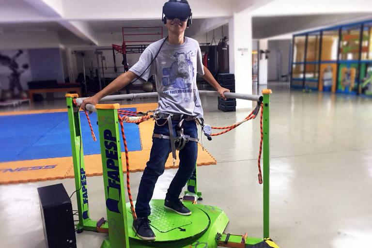 O garoto Enzo, 13, faz demonstração do tratamento de postura e equilíbrio no aparelho criado por seu pai, Dalton Kina