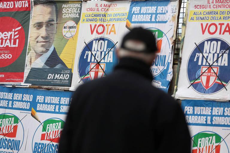 Homem vê cartazes de partidos políticos em muro de Nápoles; leis e agência melhoram posição italiana em índice anticorrupção