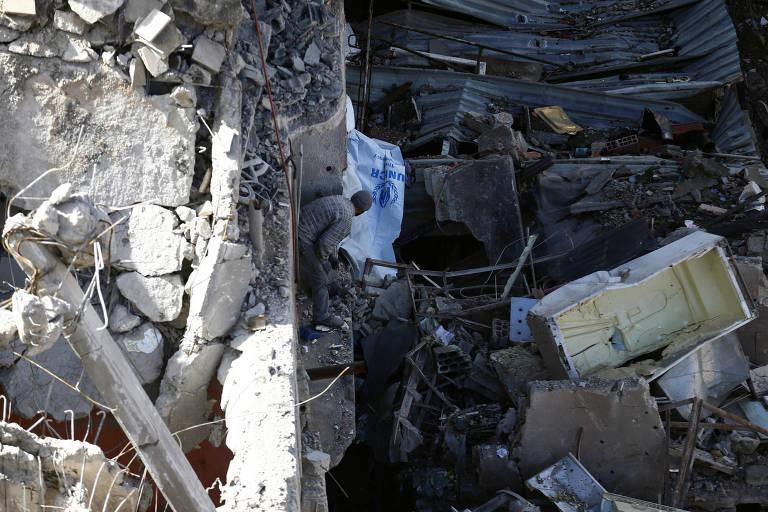Homem procura pertences em ruínas de prédios de Douma, no reduto rebelde de Ghouta Oriental, na Síria