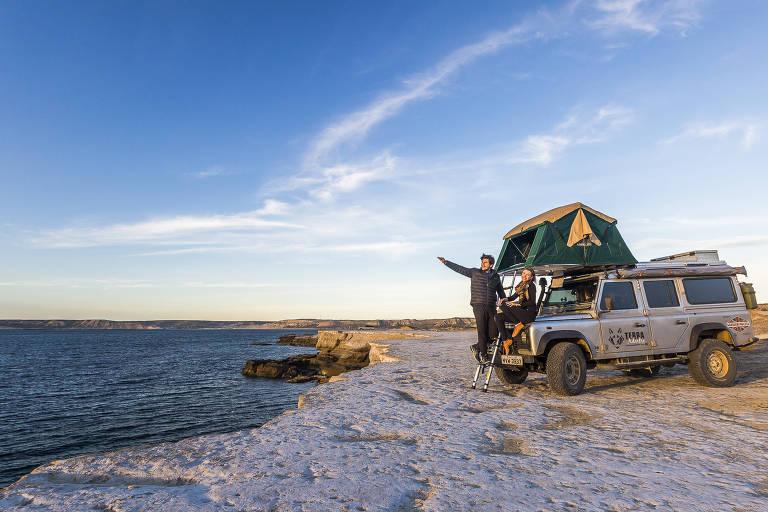 Casal na frente de carro parado em frente à água