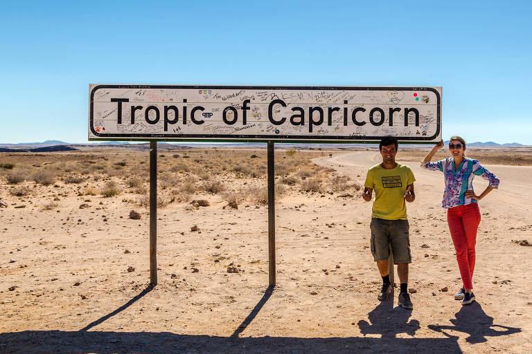 Casal na frente da placa do trópico de capricórnio, sobe areia. Céu azul