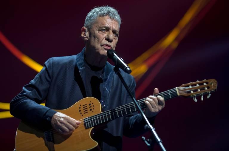 Chico Buarque segura o violão e canta ao microfone