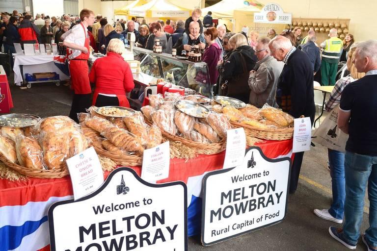 Pães expostos em barracas, com pessoas ao redor. Na frente dos pães, uma placa diz Welcome to Melton Mowbray