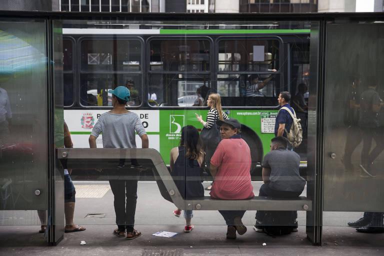 Passageiros aguardam ônibusm em ponto da avenida Paulista