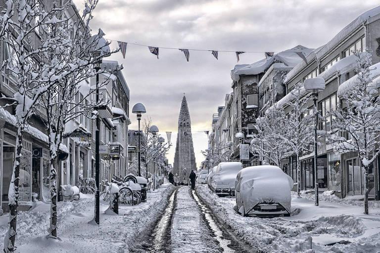 Rua com neve, ao final dela se vê uma igreja em formato de cone