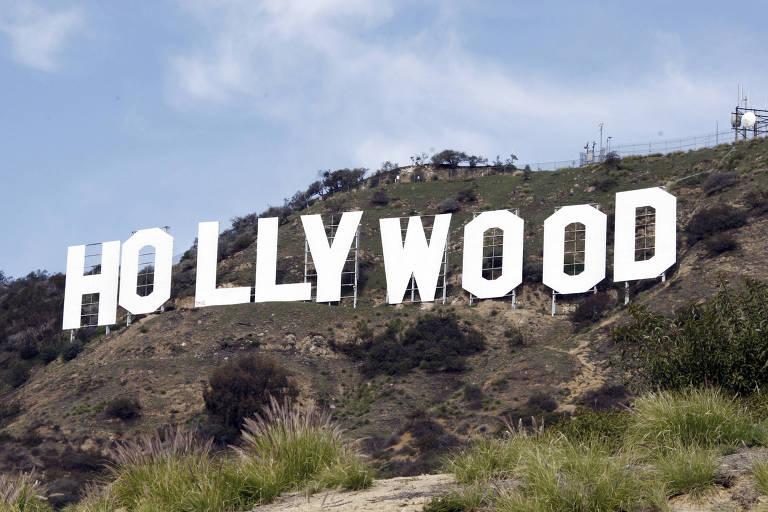 Letreiro de Hollywood é mostrado de perto, em morro de Los Angeles. As colinas são parcialmente cobertas de vegetação rasteira e arbustos.