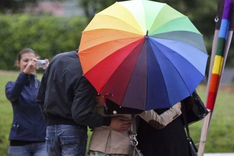 Grupo com guarda-chuva colorido contra homofobia
