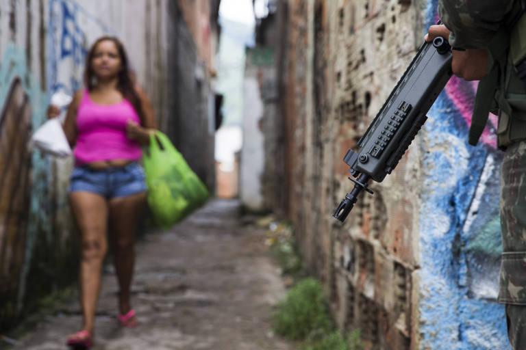 Mulher caminha com sacolas em viela por trás de imagem do fuzil de um soldado do exército