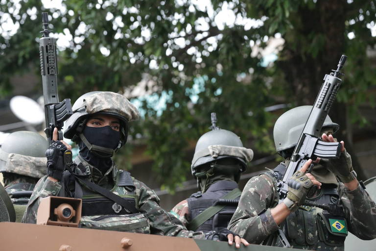 Militares das Forças Armadas com os rostos cobertos e com armas nas mãos durante operação na Vila Aliança