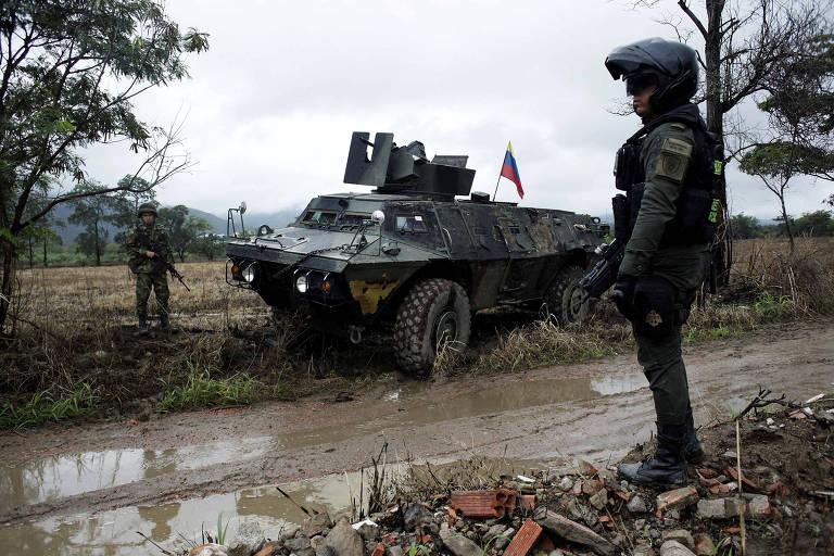 Soldados colombianos fazem guarda ao lado de blindado durante patrulha de estrada de terra perto de Cúcuta, na fronteira com a Venezuela