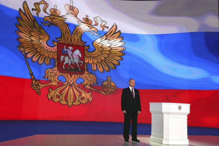 Homem parado em cima de um palco com bandeira russa ao fundo