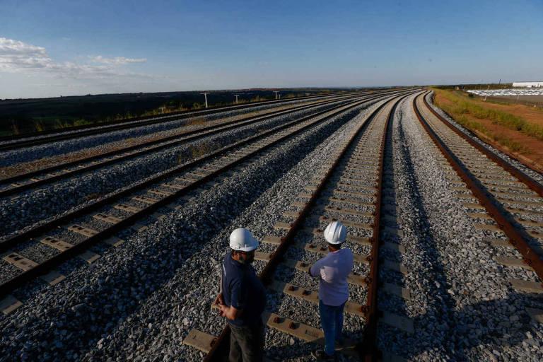 Trecho da ferrovia Norte-Sul em Anápolis (GO), com dois operários de costas no meio dos trilhos