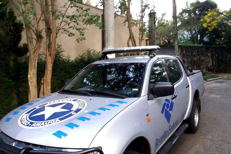 Carro da Receita Federal em frente a muro de casa em São Paulo