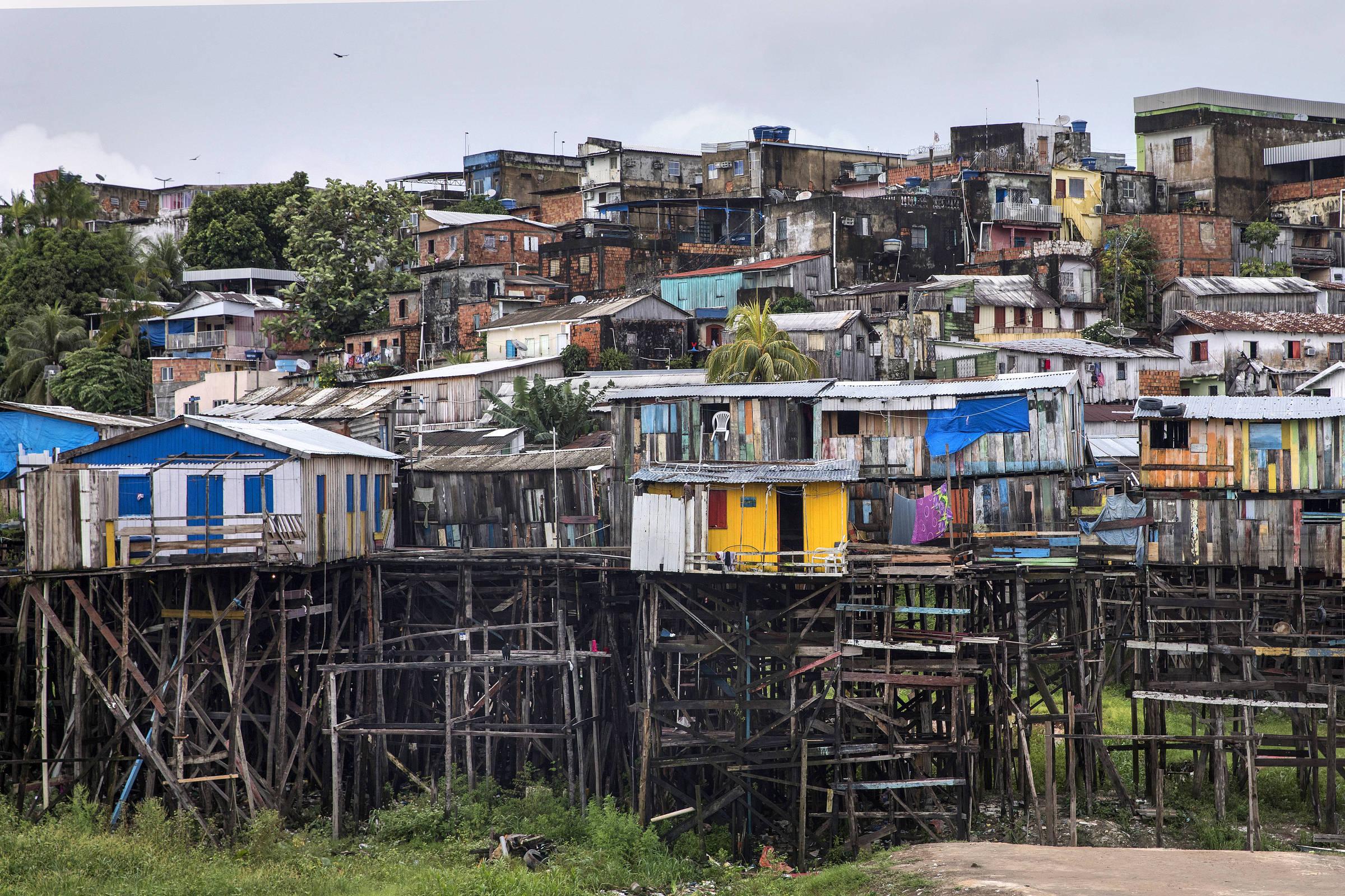 Fileiras de palafitas, casas construídas elevadas sobre estruturas de madeira, algumas coloridas, em frente a casas de alvenaria, no bairro Educandos, no centro de Manaus