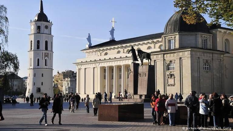 A foto mostra a praça em frente à catedral de Vilnius bastante movimentada durante uma tarde.