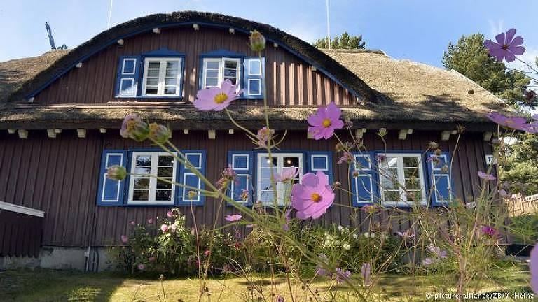 A casa tem dois andares, e o teto é tem o formato de meio círculo. A estrutura é toda de madeira, com janelas azuis. Há flores rosas plantadas em arbustos ao redor da casa