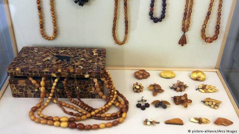 Alguns objetos de contas, como colares, broches e uma caixa, estão expostos dentro de uma caixa de vidro, com dois dos lados de madeira. Todos eles são feitos de âmbar, com tons oscilando entre o amarelo, o laranja e o marrom escuro