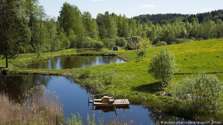 A foto mostra uma parte do parque Trakai, em que há dois lagos tranquilos cercados por uma colina coberta de grama. No fundo da imagem, há um grande bosque
