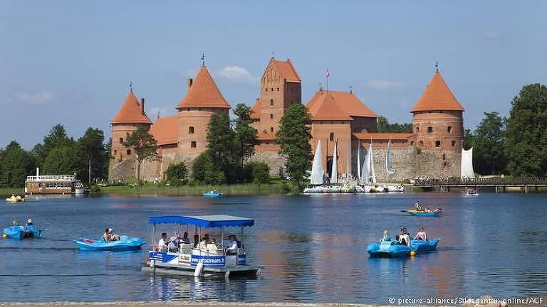 A foto mostra um pequeno castelo de tijolos vermelhos ao fundo, rodeado por um grande lago. No lago, pessoas passeiam em botes e pequenas lanchas
