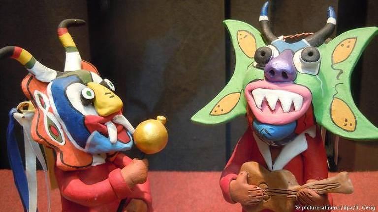 A foto mostra duas imagens feitas de barro que representam o diabo na cultura local. O da direita toca um violão e tem um chifre em cima dos olhos e duas meias luas ao lado das bochechas. O da direita também tem dois chifres na cabeça, e segura um mastro.