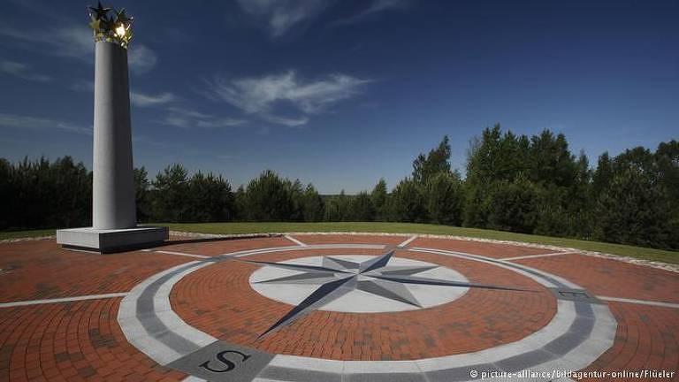 A foto mostra a área considerada o centro geográfico da Europa, com uma rosa dos ventos desenhada em cerâmica no chão e uma coluna com estrelas no topo para marcar o lugar