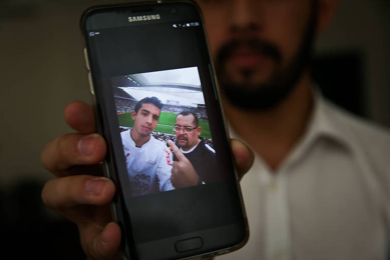 Andrey mostra foto de pai no celular