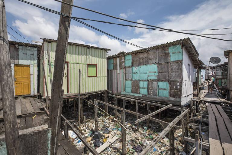 Lixo acumulado entre casas de palafita no bairro Raiz, em Manaus