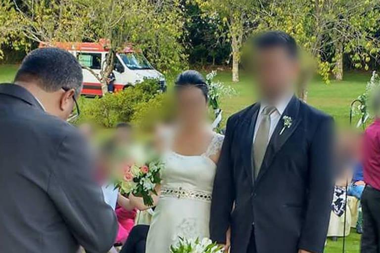 Foto dos noivos diante do padre mostra ambulância estacionada atrás deles