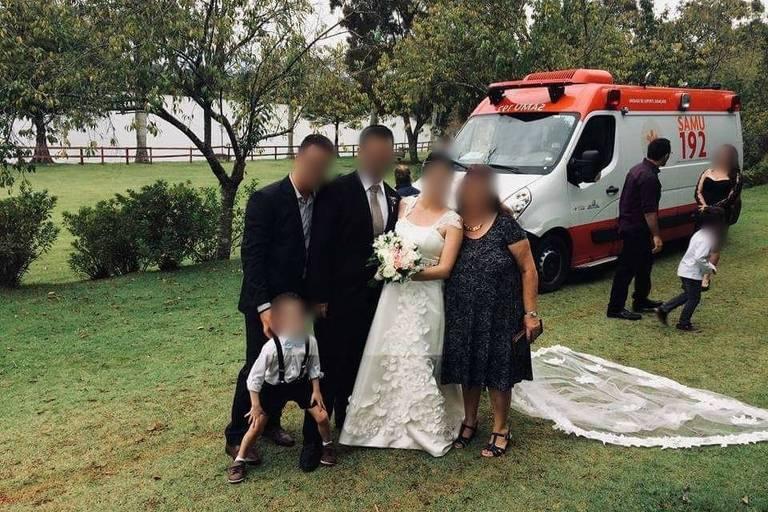 Noivos posam ao lado de convidados com ambulância do Samu ao fundo