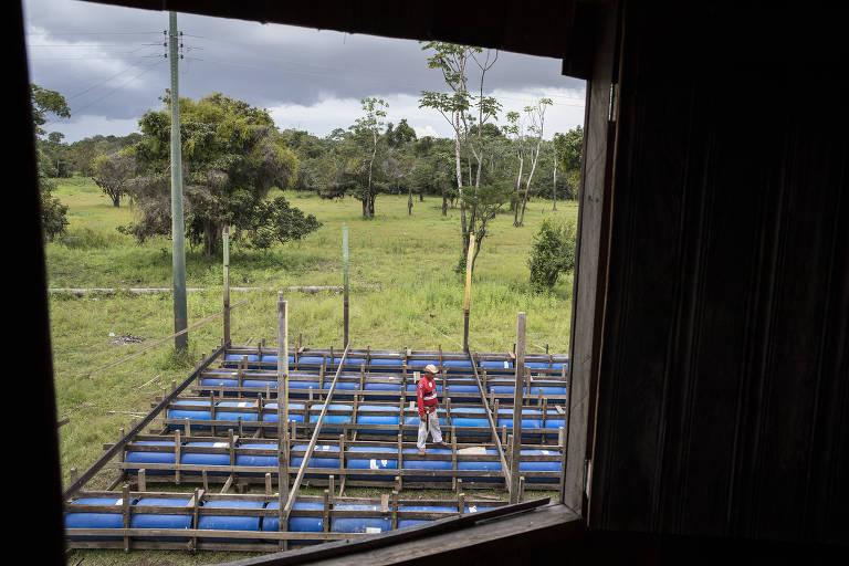 Evandro Rocha de Oliveira, 55, caminha sobre tambores plásticos que usará para construir casa flutuante