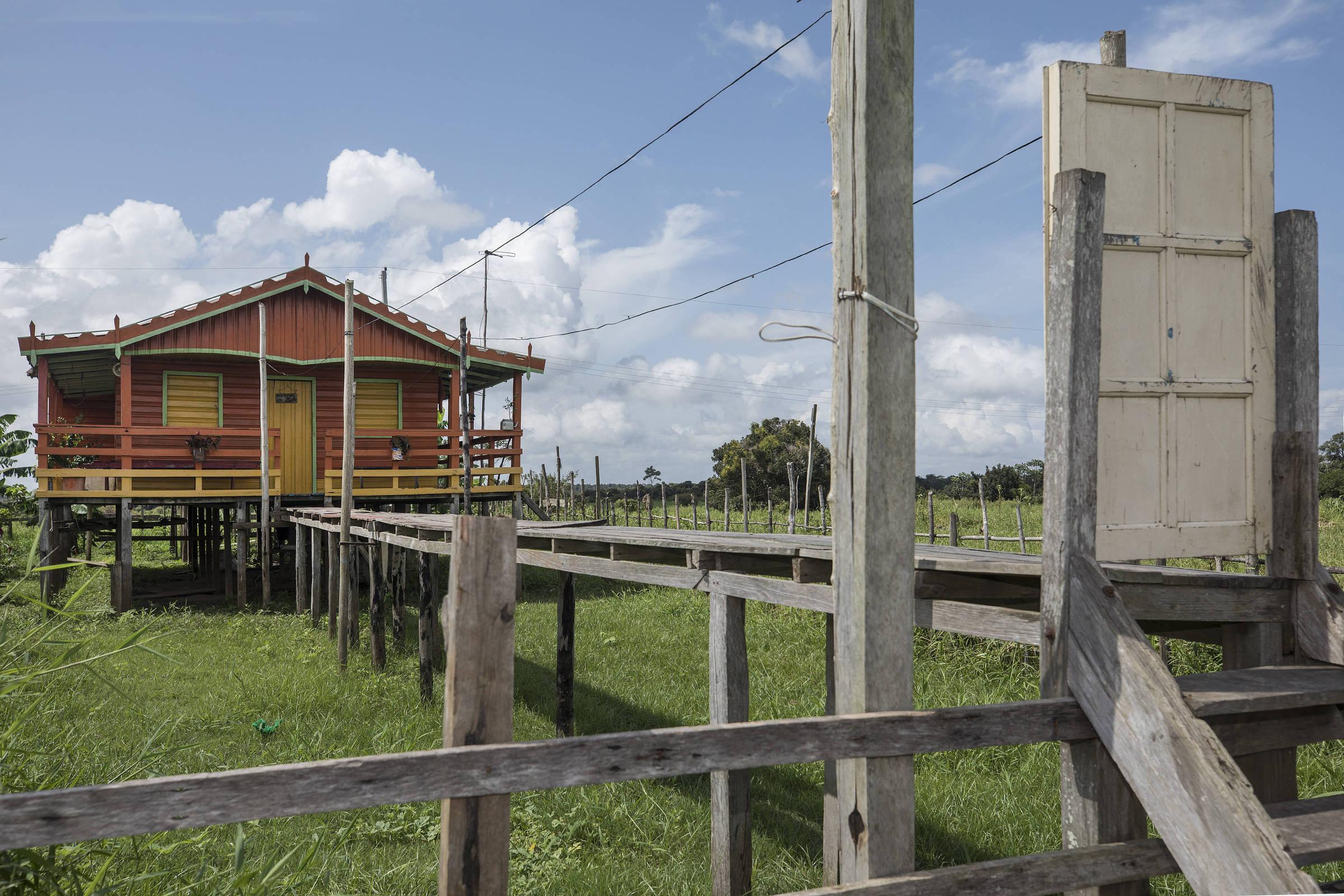 Em casa na comunidade Marimba, erguida para evitar cheias do rio Amazonas, a ponte que dá acesso à casa tem uma porta sem paredes