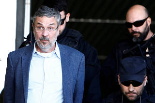 FILE PHOTO: Palocci, former finance minister and presidential chief of staff in recent Workers Party governments, is escorted by federal police officers as he leaves the Institute of Forensic Science in Curitiba