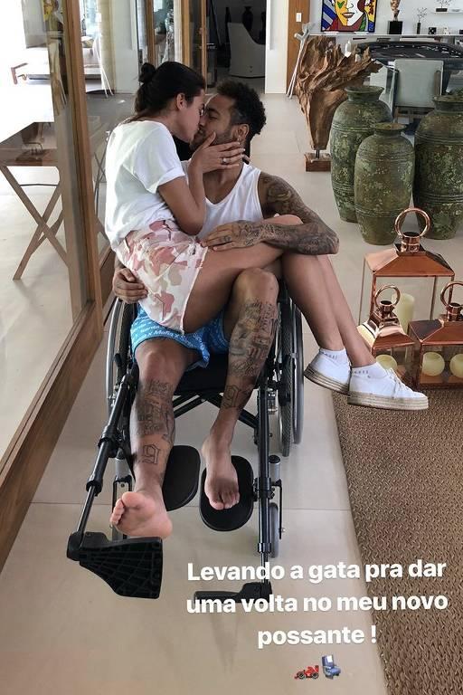 Neymar posta foto sentado em uma cadeira de rodas e beijando a namorada, Bruna Marquezine, sentada em seu colo